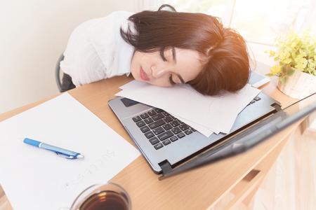 Jonge vermoeide vrouw bij bureauslaap met ogen gesloten slaapontbering en het belastende het levensconcept. Hard werken.