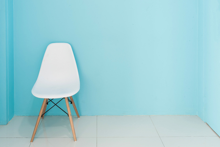 Modern white chair in a living room with blue wall with empty space for interior decorating or copyspace background.