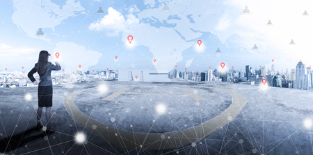Businesswoman standing on top of business building and looking forward to city with network connection on map in the sky and sunlight. International business, world wide connecting technology concept.