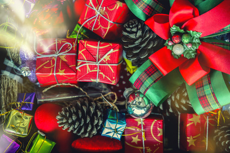 Merry Christmas holiday background concept. Closeup of red gift boxes with decorated accessories stacked on ground. Stock fotó