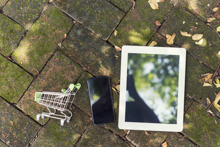 Online shopping by internet technology, modern business gadget. Connection concept with free copy space. Mobile and tablet on old brick pattern with green moss.