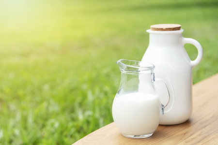 Fresh milk on wood table with green nature background. Stock fotó