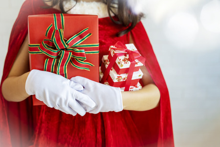 Merry Christmas festival background concept. Closeup of young sandaclaus in red clothes holding gift boxes with free copy space.