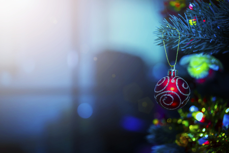 Merry Christmas background concept. Closeup of red ball hanging on Christmas tree with blurred light from window. Holiday party.