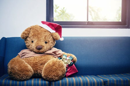 Big bear with Christmas hat and red gift box on sofa. Merry Christmas background concept.