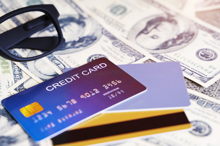 Closeup of blue credit card with blurred dollars on background. Business and finance concept.