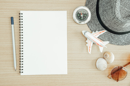 Summer travel and vacation background concept. Blank paper on table with compass, seashell, sunglasses, airplane model and hat on wood table. Stock fotó