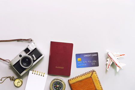 Business and travel concept. Flat lay of accessories, camera, watch, compass, passport, wallet, credit card and airplane model on white table with free space for text.