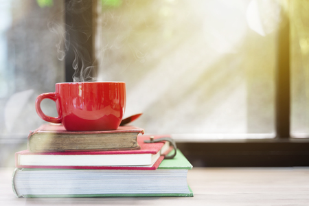 Red coffee cup with smoke on top of stacked old books on wood table with window light. Merry Christmas concept background. Resting, relaxing time or reading. Stock fotó