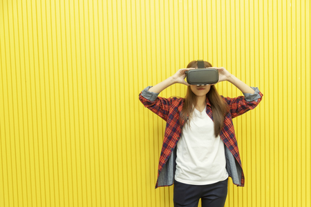 Young woman using VR head set to see the 3D movies. Modern technology for home entertainment.