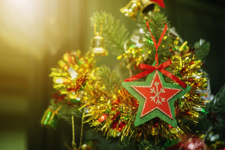 Merry Christmas background concept. Closeup of red star with green frame hanging on Christmas tree with blurred golden light from window. Holiday party.