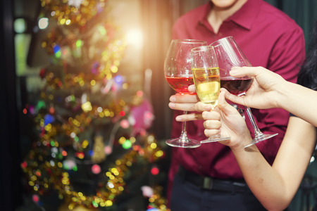 Cheerful friends clinking glasses in holiday party or celebration times event.