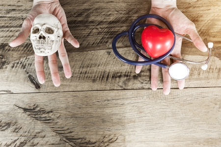 Stethoscope and red heart on left hand, skull on right hand. Choosing healthcare and die concept with free copy space for text. Stock fotó
