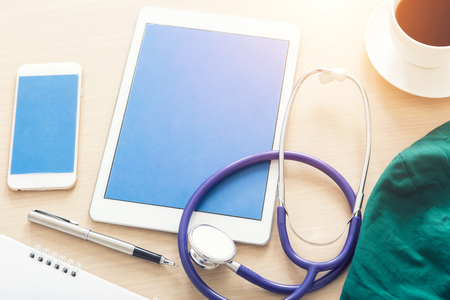 Blank screen tablet with medical objects on a desk as a metaphor for electronic diagnostic or healthcare mobile apps. Medical background.