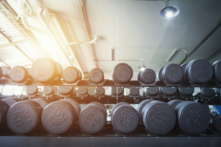 Row of dumbbells in sport club. Exercise in gym for healthy concept.