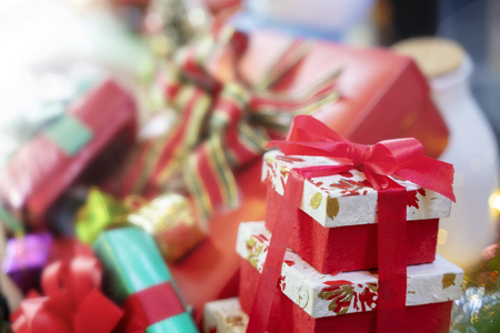 Merry Christmas background concept. Closeup of red gift box with blurred another gift boxes in background. Stock fotó