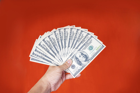 Closeup of hand holding dollars with red background. Business and finance concept. Stock fotó