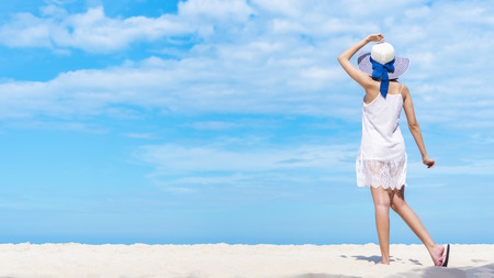Beautiful woman walking on the beach with blue sky. Happy summer vacation. Picture for add text message. Backdrop for design art work.