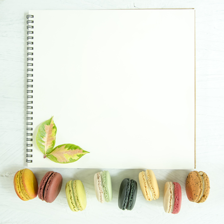 Colorful macaroons and leaves with empty page of open white notebook on table.