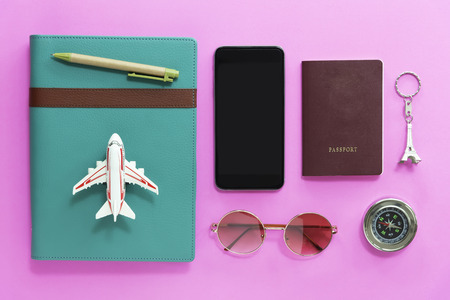 Travel concept. Closeup of mobile, passport, compass, sunglasses, airplane model and notebook on pink background. Vacation and holidays. Stock fotó