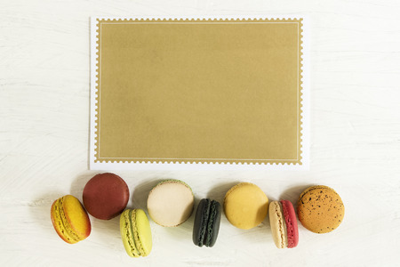 Food background, colorful french macaroons row on white background with empty brown paper for text. Stock fotó