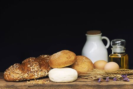 Breads, milk and oil on wood table with black background.
