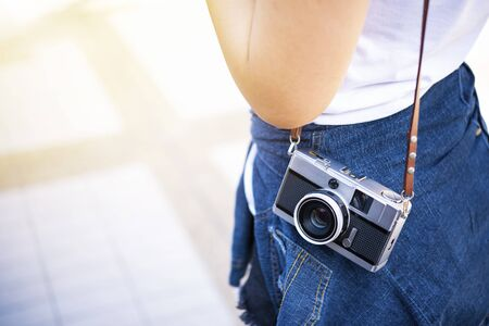 Closeup of traveler carrying camera with free copy space. Travel and lifestyle background. 写真素材