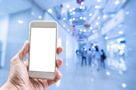 Technology background, hand holding mobile with empty screen and blurred shopping mall in background.