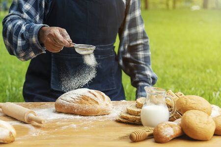 Man baking fresh bread on tray in garden with nature background.