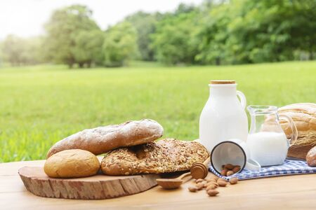 Breads and milk on wood table with blurred green garden background.