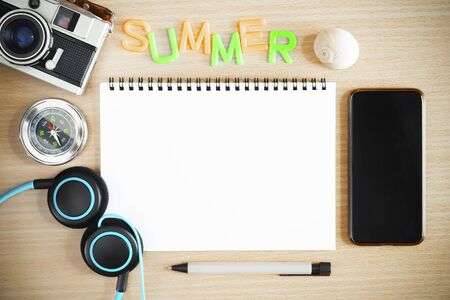 Summer background concept. Blank white paper with old camera, compass, headphone and mobile on table. Travel and vacation backdrop.