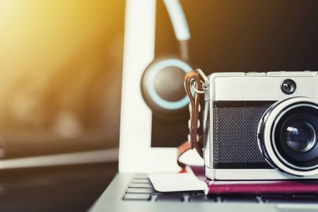 Closeup of retro film camera and headphone on passport and laptop with backlight. Photography and travel concept.