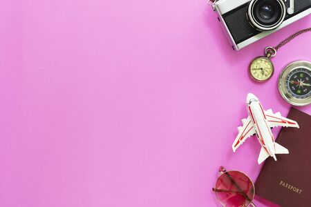 Travel and summer times concept. Flat lay of accessories, passport, sunglasses, compass, watch, airplane model and camera on pink background.