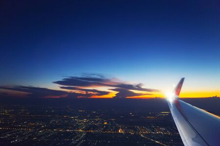 Airplane wing in the sky with cloud at sunset. Transportation, travel concept. 写真素材