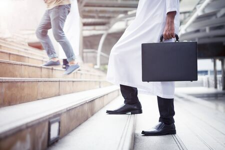 Business background concept. Arab businessman holding business bag walking up the stairs in the city.