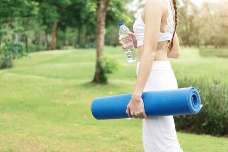 Sport and healthy people in garden concept. Closeup sporty girl holding yoga mat and water bottle walking in park or garden. Workout lifestyle in the city. 写真素材