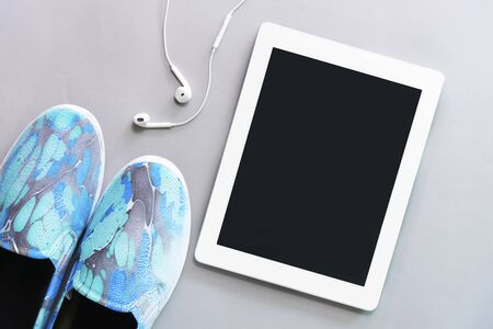 Tablet with earphone with blue sneaker on floor. Technology, listening to music and lifestyle concept.