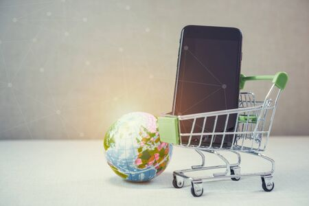 Online shopping background. E-commerce marketing technology, shopping cart on stacked mobile, tablet and laptop with connection line icon. Worldwide business. Global communication. 写真素材