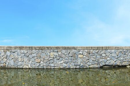 Old stone wall with water and blue sky. 写真素材
