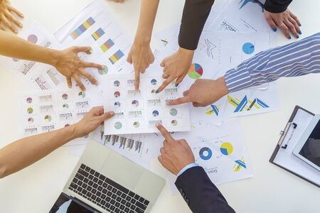 Business peoples pointing fingers to paper charts on table in meeting room. Discussion about project or job. Brainstorm for successful business concept.