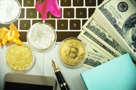 Golden bitcoins and money on laptop. Cryptocurrency and mining concept.