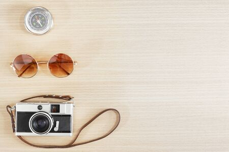 Old film camera , sunglasses and compass on wood table with free space for text. Travel and photography background concept. Happy vacation lifestyle.
