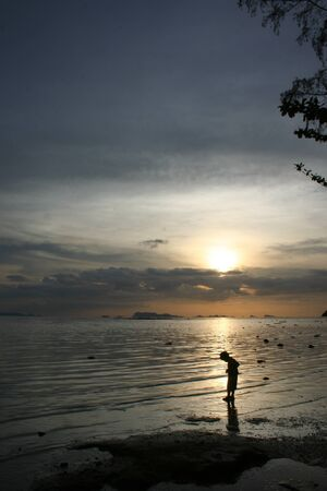 Little boy walking the beach sunset on Koh Samui. Surat Thani Province, Thailand photo