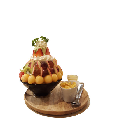 Fresh fruit Bingsu dessert,ice-cream in a cup on a wooden plate. 免版税图像