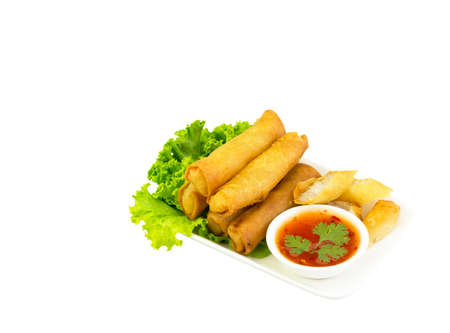 Fried spring rolls with lettuce and dipping sauce on  white plate.