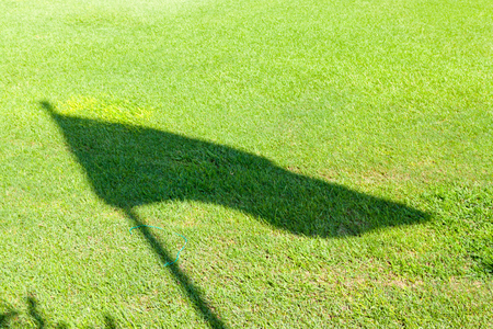 connectedness: Flag  shadow on the grass Stock Photo