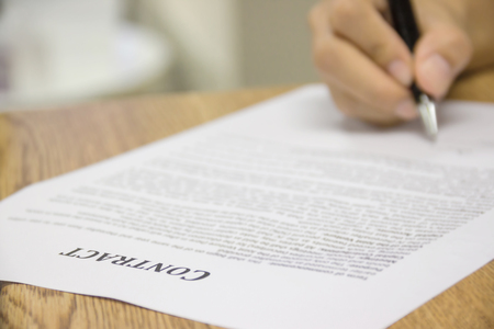 Business worker signing the contract to conclude a deal. selected focus.