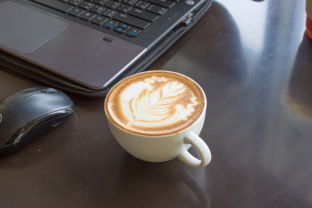 Hot latte coffee cup in a white cup on a table laptob in coffee shop. selected focus Stock Photo