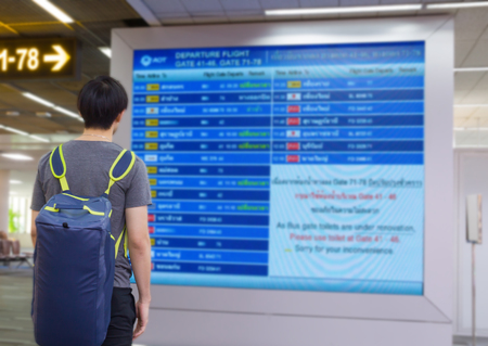 Young man with backpack in airport near flight timetable Stock Photo