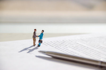 selective focus of miniature employees handshaking. Image of business contract.